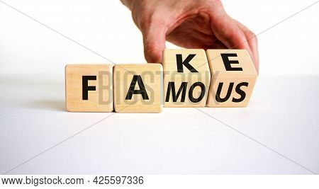 Fake Famous Symbol. Businessman Turns The Wooden Cube And Changes The Word Fake To Famous. Beautiful
