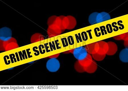 Close Up Yellow Barricade Tape With Crime Scene Do Not Cross Words Over Police Background Of Blurred