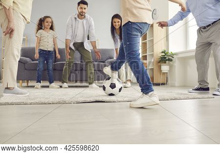 Happy Mum, Dad, Grandma, Grandpa And Children Playing Football And Having Fun At Home