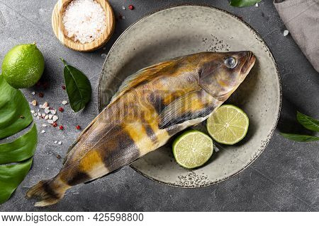 Raw Fish Sea Bass Or Lingcod And Seasonings For Cooking It On A Gray Background Top View Close Up