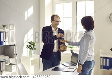 Sale Estate Agent Giving House Model And Property Key To Customer At Office