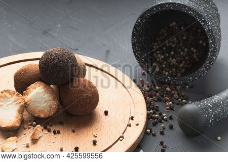 An Overturned Mortar And Pestle, Peppercorns Pour Out Of The Mortar. Cheese And Spices