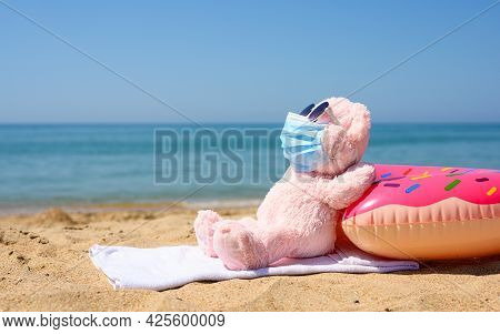 Plush Pink Melvel On The Beach Sunbathes In A Medical Mask And Sunglasses. The Concept Of Recreation