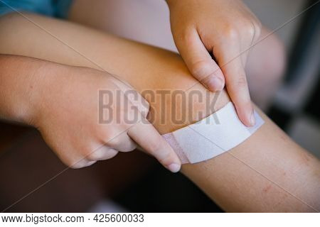A Little Boy Sticks A Band-aid On The Damaged Skin On His Leg.an Abrasion And A Scratch On The Knee.