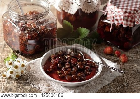 Wild Strawberry Jam In A White Small Plate With Strawberries And Leaves On A Rustic Background. Home