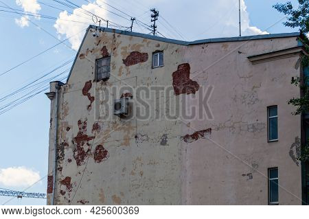 The End Facade Is A Very Old House With Small Windows And A Lone Air Conditioning. A Shabby Plaster.
