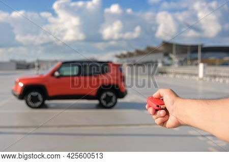 Car Key In The Drivers Hand Against The Background Of The Car Parked In The Parking Lot. Car Alarm A