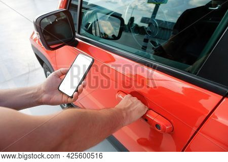 A Man Using A Smartphone Near His Car. Mobile Phone Applications For Car Lock Owners Concept