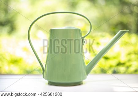 Watering Can Modern Design With Green Nature Leaf Background, Natural Colors On Wooden Shelf. Stylis