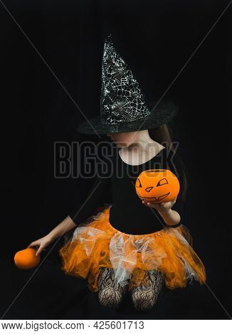 A Girl In A Witch Costume - A Hat With A Spider Web, An Orange Skirt-holds A Pumpkin Bucket For Coll