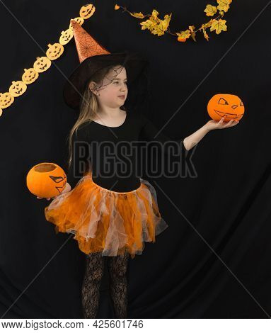 A Funny Girl With Long Hair With Two Jack Pumpkins And In A Witch Costume For Halloween Celebration