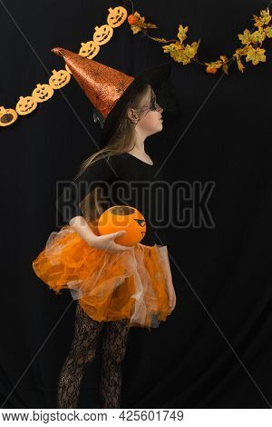 A Girl With Long Hair With A Jack Pumpkin And In A Witch Costume For Halloween Celebration On A Blac