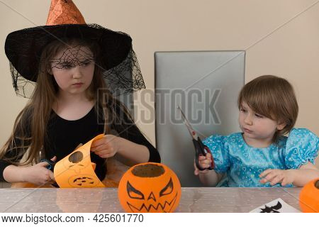 Two Girls Sisters In Costumes Of A Witch And Snow White Sitting At A Table Cut Out Paper Decorations