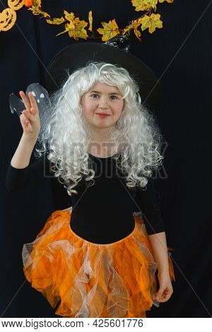 A Cheerful Girl In A White Wig And A Witch Costume On A Black Background With A Ghost Behind Her Sho