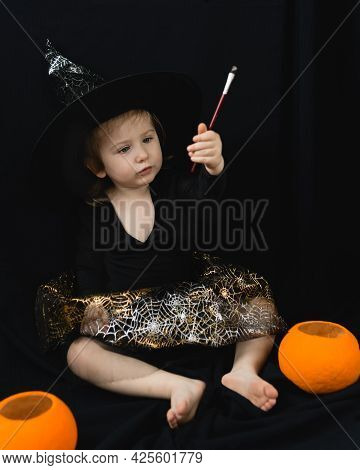 A Little Cheerful Girl In A Witch Costume-a Hat And A Skirt With A Spider Web-sits On A Black Backgr