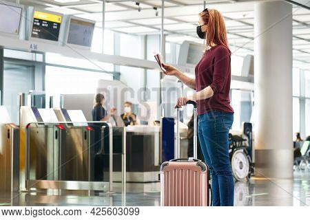 Young Woman With Protective Face Mask, Passport And Airline Tickets At The International Airport