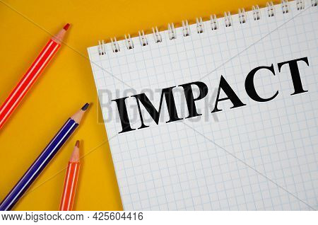 Impact Written On White Notepad And Yellow Background
