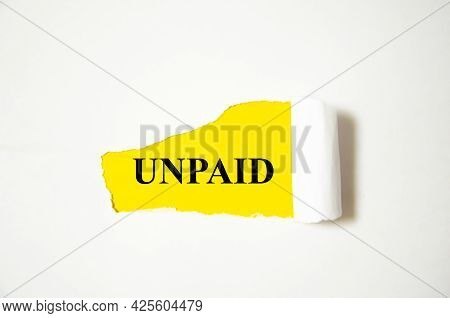 Unpaid The Text Is Written On A White Background And A Yellow Piece Of Paper