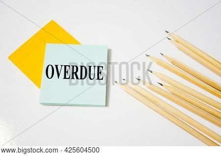 Overdue Word Written On A Yellow Piece Of Paper And White Background With Pencils Lying Next To It