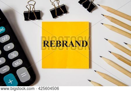 Rebrand The Word Is Written On A Yellow Piece Of Paper On A White Background Near A Calculator And A