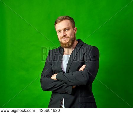 A Man In A Black Jacket Has His Arms Crossed Over His Chest And Is Looking At The Camera. Caucasian