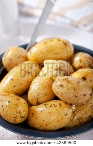 Boild New Baby Potatoes In A Bowl With Spoon, Herbs, And Melting Butter.