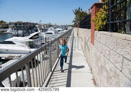 Being Active. Active Kid Run On Promenade. Energetic Boy Enjoy Running. Summer Activity. Having Fun