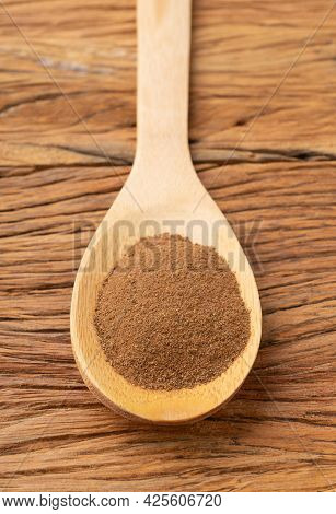 Closeup Of Ground Cumin On A Spoon Over Wooden Table.