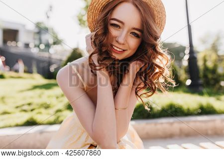 Glamorous Female Model With Ginger Hair Posing With Cute Smile On Nature Background. Outdoor Photo O