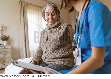 Young Nurse Is Caring For An Elderly 80-year-old Woman At Home, Helping Her And Giving Her Treatment