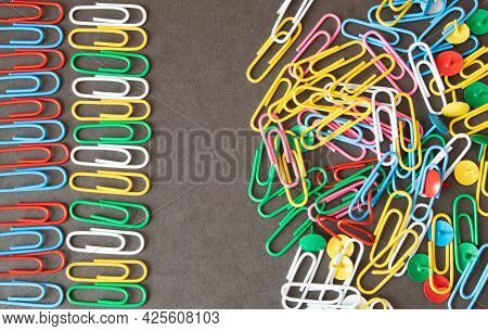 The Concept Of Order And Chaos. Chaotic Disorganized Colorful Paper Clips And To Order The Metal Pap