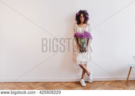 Full-length Portrait Of Positive African Woman Standing With Vase Of Flowers. Indoor Photo Of Stylis