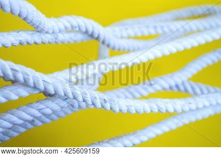 White Rope On A Yellow Background. Rope Close-up. The Rope Sections Are Taut.