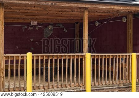 A Patio Smoking Area With Wooden Rails And Vintage Decor Peeling Paint