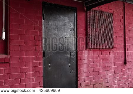 A Vintage Retro Black Steel Painted Door And Red Brick Wall With Vent