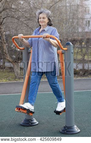 Grandma Is Doing Exercises. Gray-haired Elderly Woman On The Playground. An Elderly Woman In The Fre