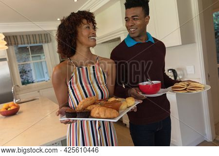 Happy african american couple preparing food for breakfast for family and smiling. family enjoying quality free time together.