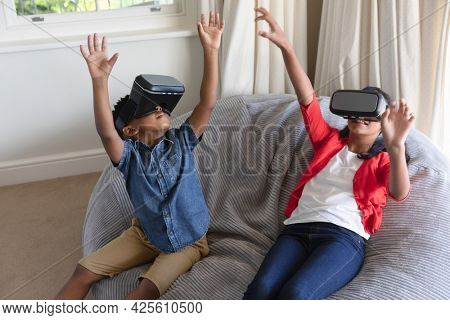 Happy african american boy and girl using vr headsets and smiling at home. childhood with technology, spending free time at home.