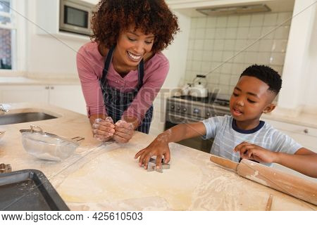 Happy african american mother with son baking in kitchen, cutting cookies. family enjoying quality free time together.