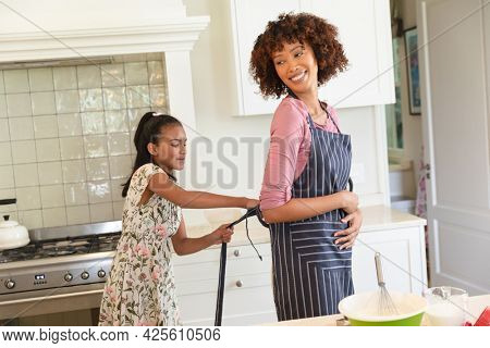 Happy african american mother and daughter putting on aprons before baking in kitchen. family enjoying quality free time together.