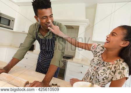 Happy african american father and daughter having fun baking in kitchen. family enjoying quality free time together.