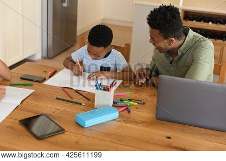 Happy african american father with daughter and son doing homework at home smiling. family domestic life, spending time working together at home.