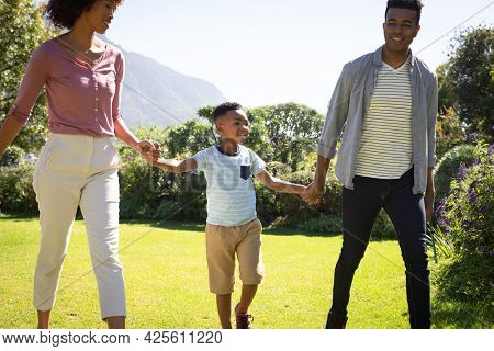 Happy african american couple with son outdoors, walking in sunny garden. family enjoying quality free time together.