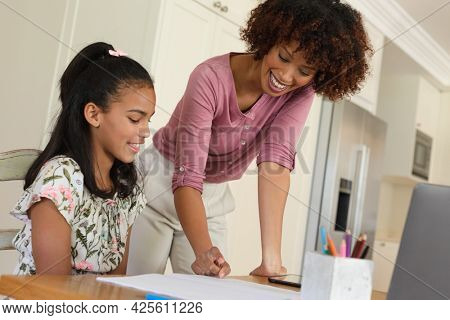 Happy african american mother and daughter doing homework at home smiling. family domestic life, spending time learning together at home.