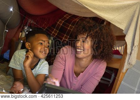Happy african american mother with son at home, lying in blanket fort and using tablet. family enjoying quality free time together.