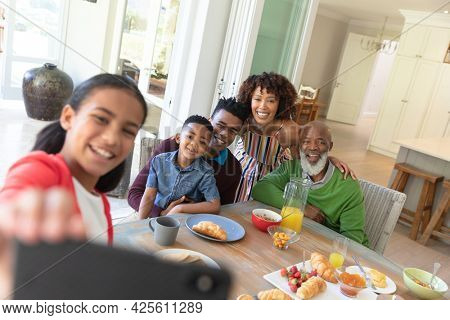 Happy african american family sitting at breakfast table taking selfie with smartphone and smiling. family enjoying quality free time together.