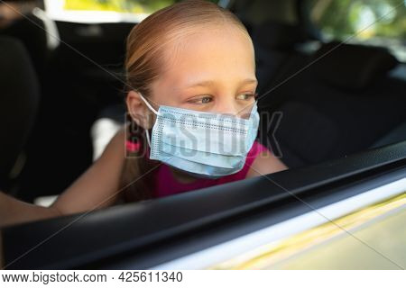 Caucasian girl wearing face mask and sitting in car looking through window. medical precautions, lifestyle during covid 19 pandemic.