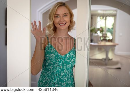Portrait of happy caucasian woman at home, smiling and waving hand. enjoying quality free time at home.
