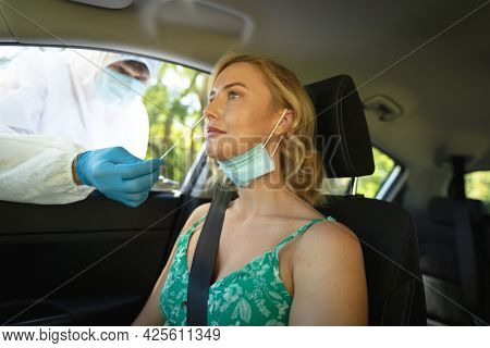 Medical worker wearing ppe suit taking swab tests of caucasian woman sitting in car. medical and health precautions, lifestyle during covid 19 pandemic.