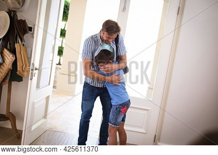 Happy caucasian father with son at home, smiling and embracing. family enjoying quality free time together.